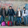 Happy teenage friends with school bags and skateboards standing in front of — Stock Photo #9097757