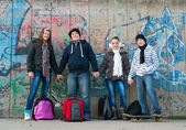 Happy teenage friends with school bags and skateboards standing in front of — Stock Photo