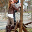 Young couple kissing on the children playground on cloudy autumn day — Stock Photo
