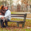Young couple kissing while sitting on the bench in the park on cloudy autumn day — Foto de Stock