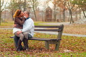 Young couple kissing while sitting on the bench in the park on cloudy autumn day — Stock Photo