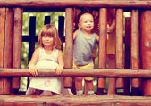 Photo in sepia tones of brother and sister playing on the playground — Stock Photo