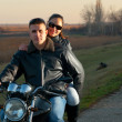 Young happy couple riding a motorcycle at sunset on beautiful autumn day — Foto Stock #9346426