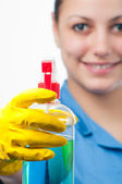 Close up of bottle of detergent in gloved hand of the cleaning lady isolated on white — Stock Photo