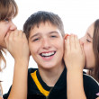 Two teenage girls sharing a secret with teenage boy — Stock Photo