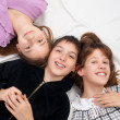 Two smiling teenage girls and one smiling teenage boy resting on bed — Stock Photo