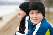 Cute smiling teenage boy outside with friends in the background on cloudy autumn day — Stock Photo