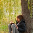 Stock Photo: Pretty teenage girl reads the book under the willow tree