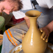 Craftsman making vase from fresh wet clay on pottery wheel — Stock Photo #9628028