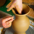 Craftsman making vase from fresh wet clay on pottery wheel. — Stock Photo #9628241