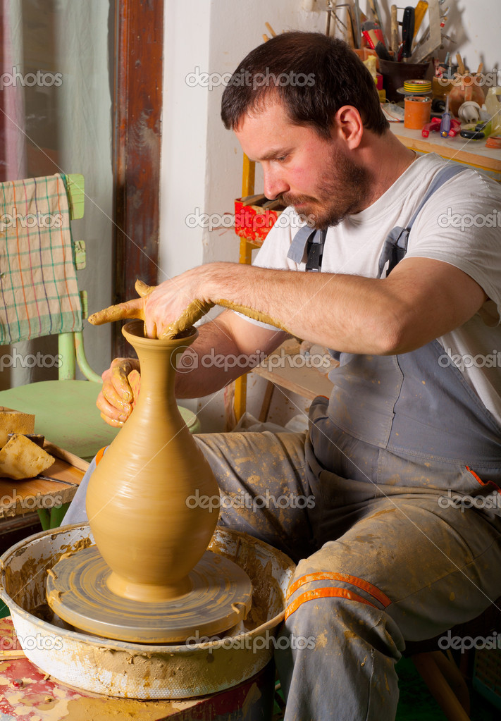 Craftsman making vase from fresh wet clay on pottery wheel — Stock Photo #9627866