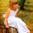Painting showing portrait of cute little girl sitting on the log in the forest — Stock Photo #9740340