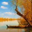 Landscape painting showing old wooden boat on the river on sunny spring day - Stock Photo