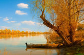 Landscape painting showing old wooden boat on the river on sunny spring day — Stock Photo