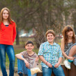 Happy teenage boys and girls spending time together in the park on beautiful spring day — Photo