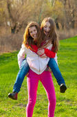 Happy teenage girls piggy back riding on the beautiful sunny spring day — Stock Photo