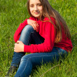 Beautiful teenage girl sitting in the grass on sunny spring day — Stock Photo #9899463