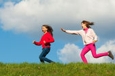 Two happy teenage girls running on the meadow on sunny spring day — Stock Photo