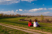 Two teenage girls sitting in the grass and talking on beautiful sunny spring day — Stock Photo