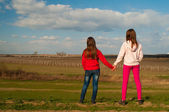 Two teenage girls standing and holding hands while watching the nature on beautiful sunny spring day — Stock Photo