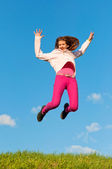 Cute teenage girl jumping with joy on sunny spring day — Stock Photo