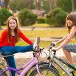 Two pretty teenage girls having fun on the bicycles in the park on beautiful spring day — Stock Photo