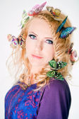 Beautiful woman with butterflies in hair — Stock Photo