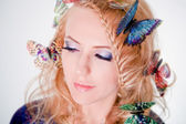 Face of a beautiful woman butterflies in hair — Stock Photo