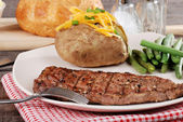Barbecue steak with baked potato and cheese — Stock Photo