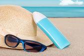 Suntan lotion hat focus on sun glasses — Stock Photo