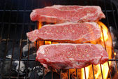 Barbecuing strip loin steaks — Stock Photo