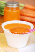 Macro carrot baby food on spoon — Stock Photo