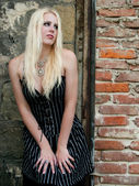 Blond gothic girl in front of a brick wall — Stock Photo