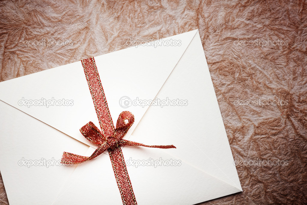 Close up of a envelope with a red ribbon on a paper background — Stock Photo #9297002