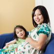 Pregnant Asian mother and her daughter — Stock Photo