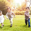 Asian kids running in park - Stockfoto