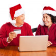 Senior Asian couple shopping online celebrating Christmas - Foto Stock