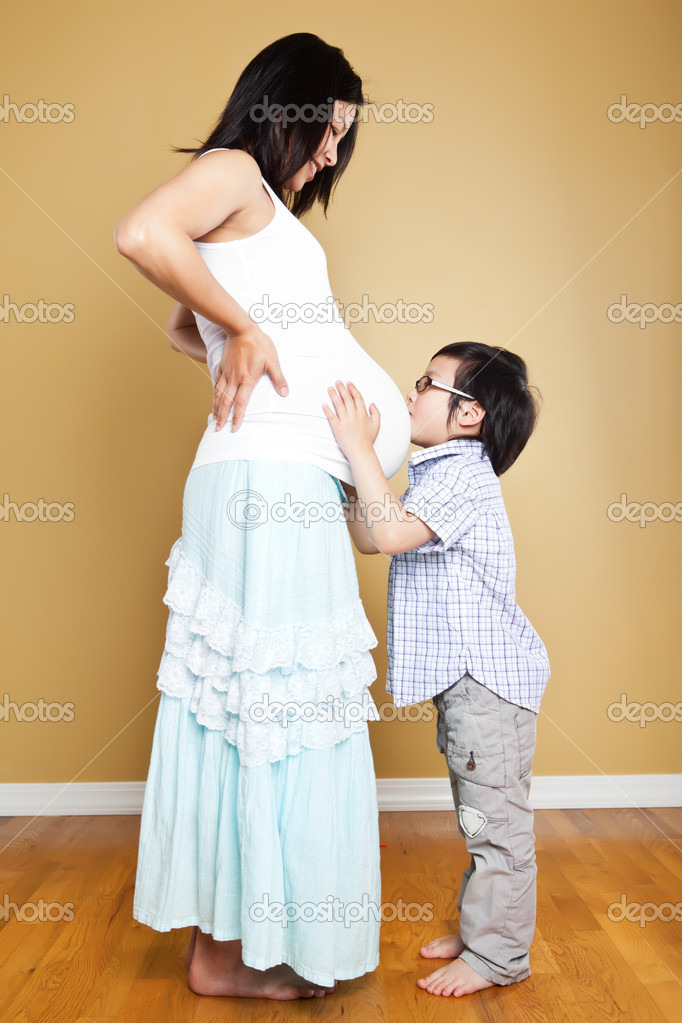 A shot of an Asian boy kissing the belly of his pregnant mother — Stock Photo #8806899