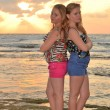 Two girls blonde on the beach at sunset — Stock Photo
