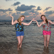 Stock Photo: Two girls blonde on the beach at sunset