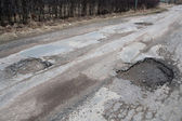 Damaged asphalt road after winter. — Stock Photo