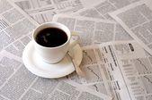 Coffee over newspaper — Stock Photo