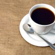 Cup of coffee on burlap - Stock Photo