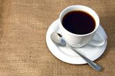 Cup of coffee on burlap — Stockfoto