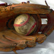 Old baseball in a glove — Stock Photo