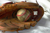 Old baseball in a glove — Stock Photo