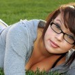 Beautiful model with glasses blue eyes laying in the grass — Stock Photo #9392065