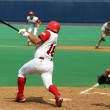 Baaeball batter swinging and hitting the ball - Stock Photo