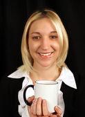 Beautiful, blonde business woman smiling holding coffee mug — Stock Photo