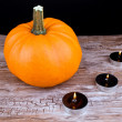 Halloween pumpkin and black candles - Stockfoto